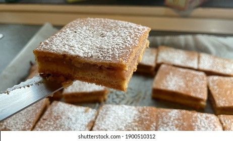 Homecooked apple pie in oven tray, woman hands cutting the fresh hot pie in portions. Powder sigar on top, closeup view