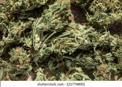 Homegrown Marijuana Buds. Cannabis Flowers on Wood Table Background.