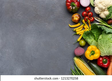 Homegrown vegetables assortment on gray concrete table, farming border, top view, copy space