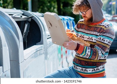 Homeles man in eyeglasses searching food in thrash can. View of hungry tramp opens pizza box. Beard beggar lost human dignity. Concept of poverty unemployment