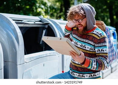 Homeles man in eyeglasses searching food in thrash can. View of tramp holding packing for pizza. Beard beggar lost human dignity. Concept of poverty unemployment