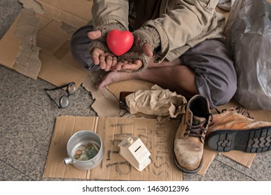 Homeless adult man sitting holding heart  on the street in the shadow of the building and begging for help and money. Problems of big modern cities. Indifference of people. Social issues.