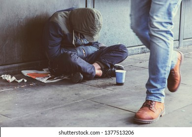 Homeless adult man sitting on the street in the shadow of the building and begging for help and money. Problems of big modern cities. Indifference of people. Social issues.