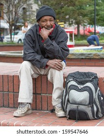 Homeless african american man sitting outdoors with backpack.