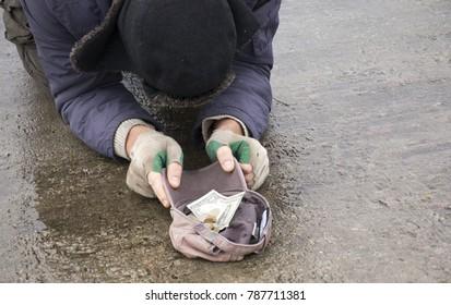 Homeless beggar asks for alms on the bridge.Beggar begging on the street.A homeless man on a city street. A homeless person.