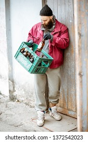 Homeless beggar bringing box with glass bottles to the collection point. Way of earning money for the poor
