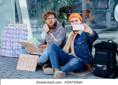 Homeless beggar opening pizza in cardboard box,young handsome beard man blogger making selfie portrait photo or video on smart phone sitting together on ground outdoors. Concept of human understanding