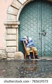 homeless beggar is sleeping on street. Homeless, dirty men sleep on asphalt streets. The social problem.
