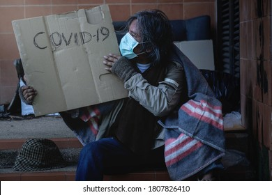 """Homeless begging man with a medical mask sits on the steps holding a brown cardboard, The word """"Covid-19"""" is on the cardboard"""