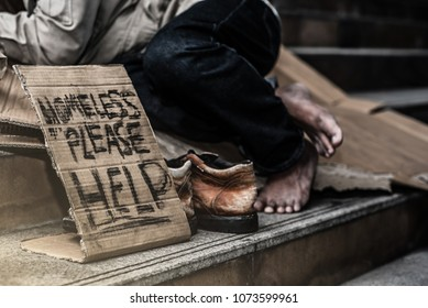 homeless begging man's hand with money in his hat on the street