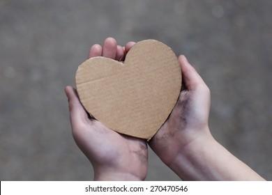 homeless boy holding a cardboard heart, dirty hand