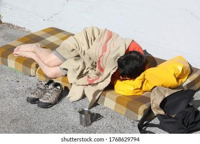 homeless bum sleeps on a filthy mattress on the city sidewalk