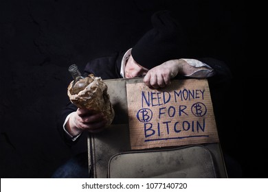Homeless business man sleeping on travel suitcase with empty bottle and cardboard bitcoin sign.