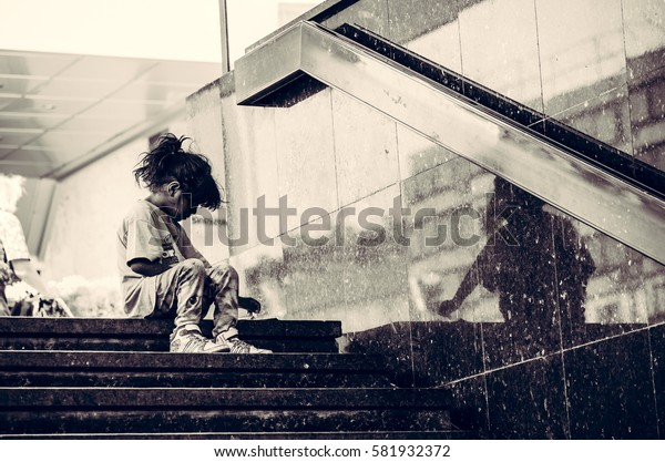 Homeless child eating on the stairway in the street. September - 16. 2016. Novi Sad, Serbia. Editorial image.