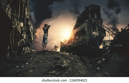 Homeless child standing and watching destroyed houses