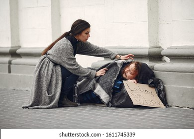 Homeless in a city. Man asking for food. Man with a tablet. Girl helping a homeless