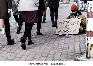 Homeless, dirty man sitting with a sign and begging for money on the street