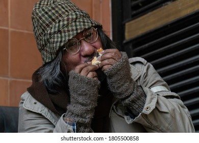 Homeless and hungry. Close up of senior man eating bread
