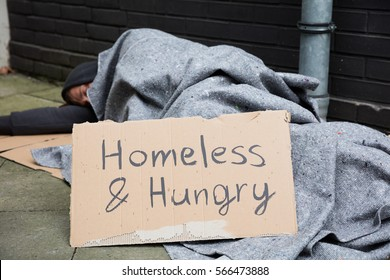 Homeless And Hungry Man Sleeping On Street With Signboard