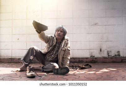 homeless and hungry vagrant holding a cup, asking for money and food