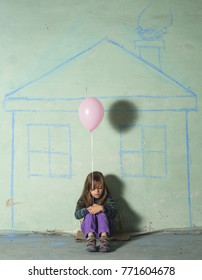 Homeless kid girl lonely sitting near the wall with pink baloon.