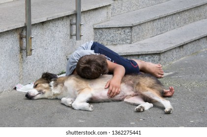 Homeless kid sleeping with his dog on the streets of Bucharest, Romania, Eastern Europe. Poor young child. Concept of poverty, cruelty, social differences and misery.