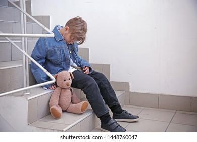 Homeless little boy with teddy bear sitting on steps