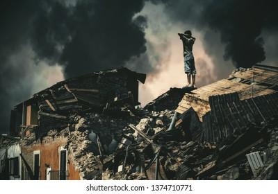 Homeless little boy watching destroyed houses and bombarded city.