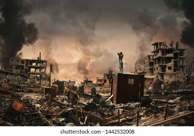 Homeless little boy watching destroyed houses and bombarded city between smoke.