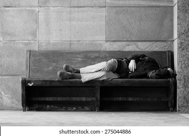 Homeless lying on a wooden bench