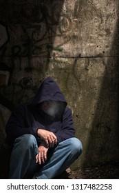 Homeless male in dark and rundown street location.