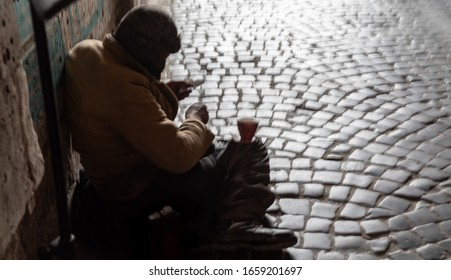Homeless man. Blurred image of a beggar sitting on the street and waiting for alms.
