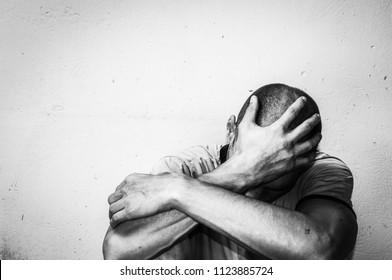 Homem sem-teto viciado em drogas e álcool sentado sozinho e deprimido na rua sentindo-se ansioso e solitário, conceito documentário social preto e branco