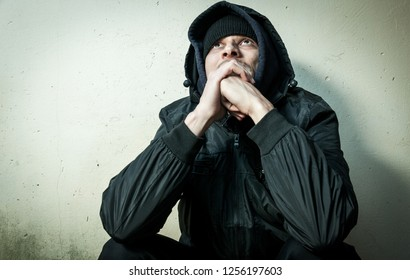 Homeless man drug and alcohol addict sitting alone and depressed on the street in winter clothes feeling anxious cold and lonely, social documentary concept dramatic image