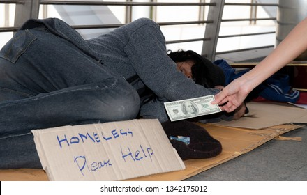 Homeless man get to sleep on floor in public path way with old hat and show Homeless please help kindness sign on cardboard in front for money donation.Kindness woman donates money to homeless beggar.