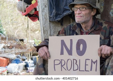"homeless man holds a paper cardboard sign that reads ""no problem"""