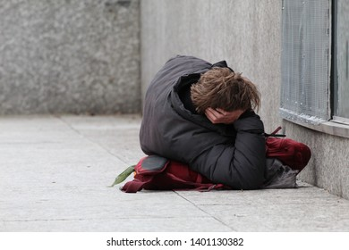 Homeless Man Laying on a Rucksack on Marble Ground Against Marble Background in Edinburgh