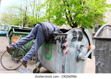 A homeless man looking for food in a garbage dumpster. / Urban Poverty
