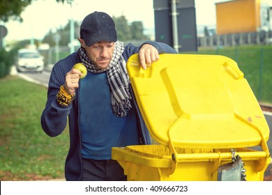 A homeless man looking for food in a garbage dumpster.