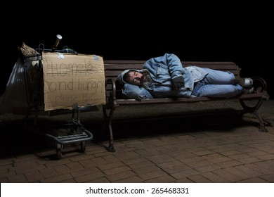 Homeless man at night sleeping on a park bench with his shopping cart full of his possessions