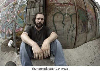 A homeless man on the city streets, filled with anxiety and hopelessness.  Shot with fish-eye lens and de-saturated.