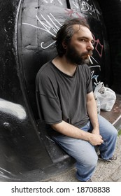 A homeless man on the city streets, filled with anxiety and hopelessness.  Shot with fish-eye lens.