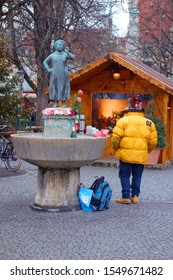 Homeless man person in yellow jacket standing next to fountain on Christmas market in Munich Germany Munchen tree time