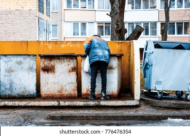 Homeless man is searching for food in garbage dumpster. Man in poverty. Man is searching something in container
