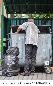 Homeless man is searching for food in the waste container. Poverty concept.