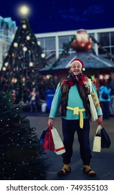 Homeless man with shopping bags stands nearby Christmas tree. Hobo is all excited about holiday sale. Blurred evening outdoors background
