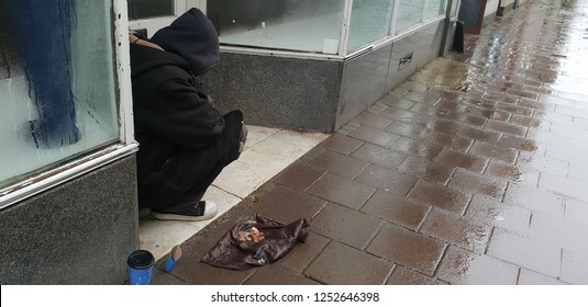 Homeless man sitting in doorway at christmas begging for money in the rain.