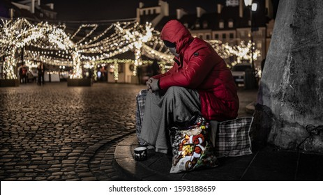 Homeless man sitting on the bag near the Old Town, floodlit by the lights of Christmas decorations.