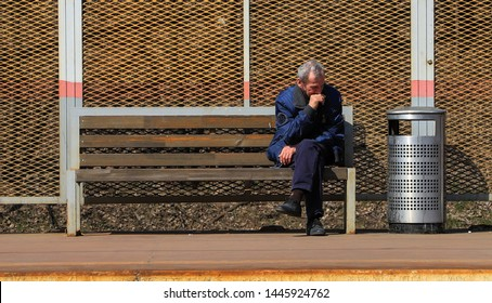 Homeless man sitting on a bench alone near trash can, thinking about life.