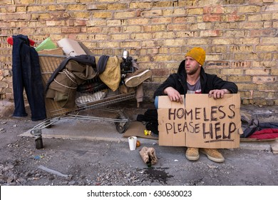 Homeless man sitting on the street, with cardboard. Homeless, please help - sign on the cardboard.